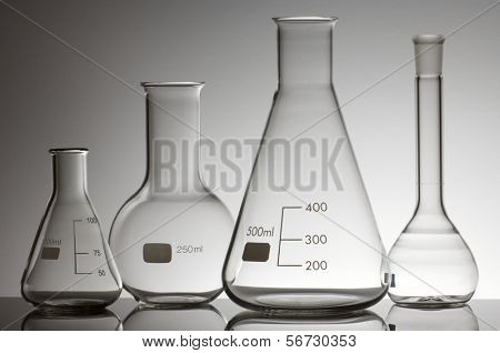 group of four empty laboratory flasks on a white background