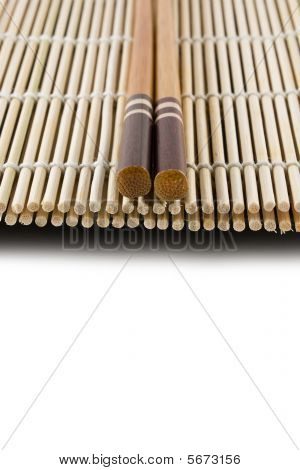 Chopsticks on a Japanese sushi rolling mat on a white surface ** Note: Shallow depth of field