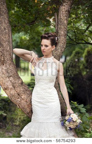 Young Bride With Bouquet Near Tree