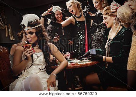 Beautiful women in evening dresses playing poker