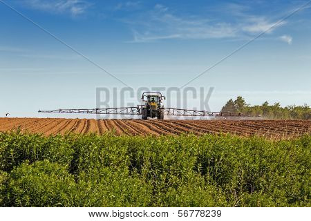A large agricultural sprayer with wide booms spraying a field of potatoes in rural Prince Edward Island, Canada.