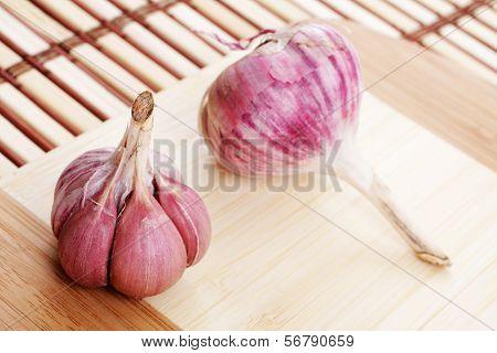 Two Heads Of Garlic On A Cutting Board