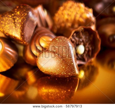Valentine Chocolates. Assorted Chocolate Candies. Chocolate Sweets. Candy Border Design over Golden Background. Heart Shaped Chocolate