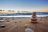 Stones balance on beach sunrise shot. Stock image poster