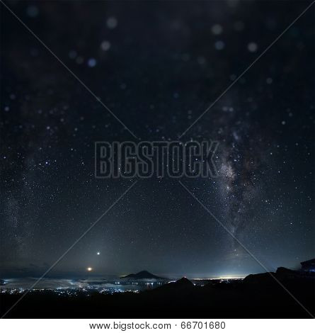 Panorama of a night sky with stars and Milky Way on equatorial latitude with mountains and illuminated town below. Tilt shift effect used