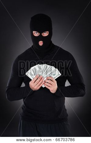 Criminal In A Balaclava Holding A Fistful Of Money