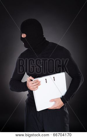 Thief In A Balaclava Stealing A File