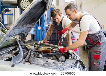 Two mechanic fixing car in a workshop