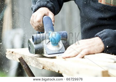 Man's arms sawing wood board in the workshop.