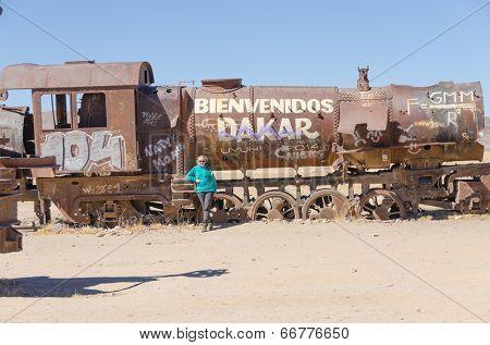 Tourist in Cementerio de trenes (Train Cemetery), Salar de Uyuni, Bolivia
