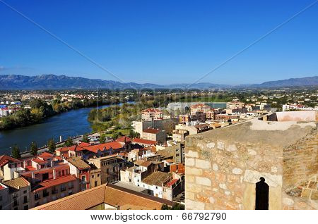 aerial view of Tortosa, Spain, and Ebro River, with the Ports of Tortosa-Beseit mountain range in the background