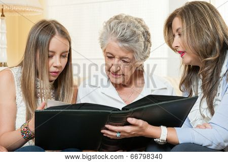Women watching family album at home