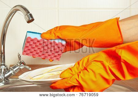Hands in gloves with dirty dishes over the sink in kitchen