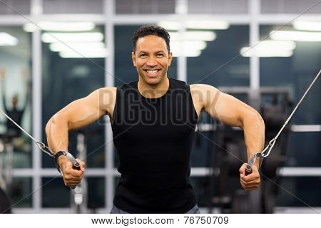 healthy bodybuilder doing triceps pull down practice in gym poster