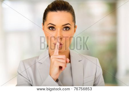 pretty young businesswoman saying shh