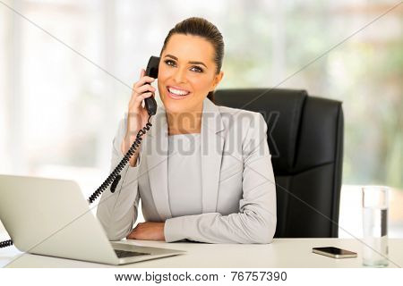 beautiful young businesswoman talking on landline phone
