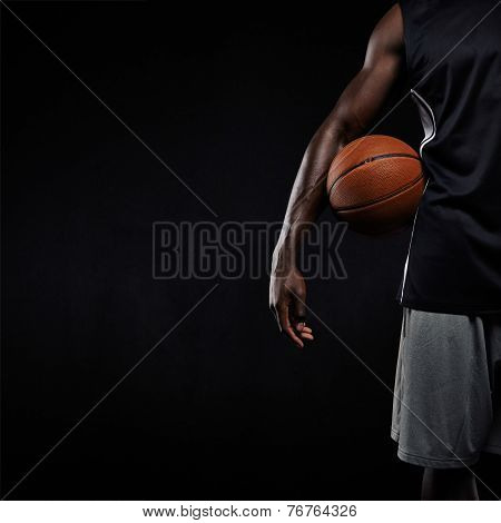 Black Basketball Player Standing With A Basket Ball