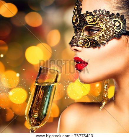 Sexy model woman with glass of champagne wearing venetian masquerade mask at party, drinking champagne over holiday glowing background. Christmas and New Year celebration. Perfect make up