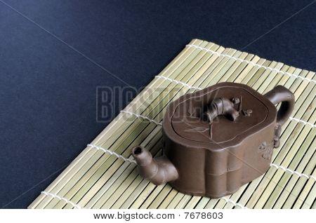 Small clay teapot on bamboo mat