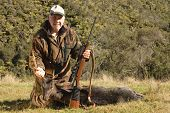 Successful hunter with a fallow deer taken in New Zealand poster