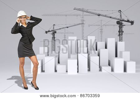 Business woman in glasses. Full lenght. Cubes with tower cranes
