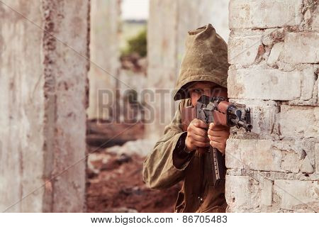 Insurgent in hood with machine gun is aiming. Ruined city background. poster