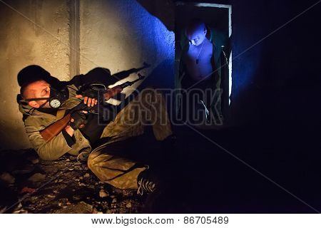 Soldier With The Rifle In The Gas Mask On The Foreground. Bloody Zombie In The Dark.
