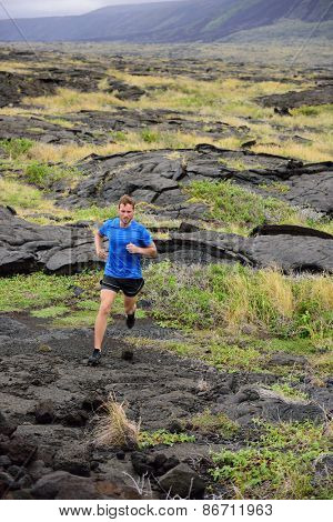 Trail Running fitness male ultra runner in nature landscape, volcanic rocks. Sport running man in cross country trail run. Male athlete exercising and training in summer outdoors.