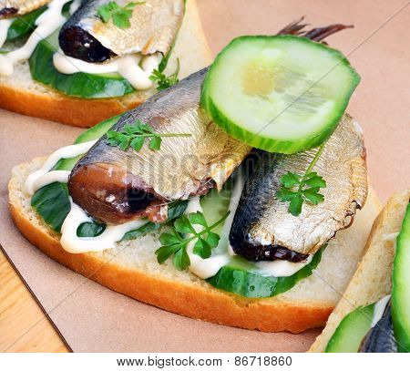 Sprats sandwiches appetizer  with vegetables on paper background poster