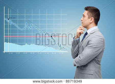 business, people, statistics, economics and crisis concept - thinking businessman in suit looking to chart making decision over blue background