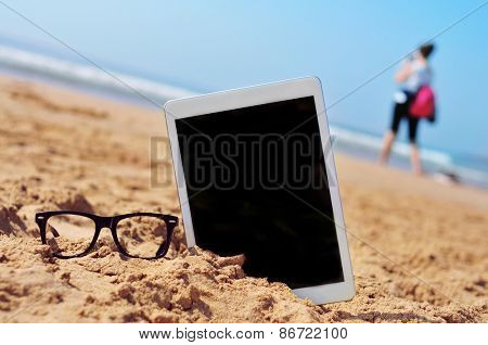 a pair of black plastic-rimmed eyeglasses and a tablet computer with a black blank space in the screen, in the sand of a beach, and a blurred woman in the background