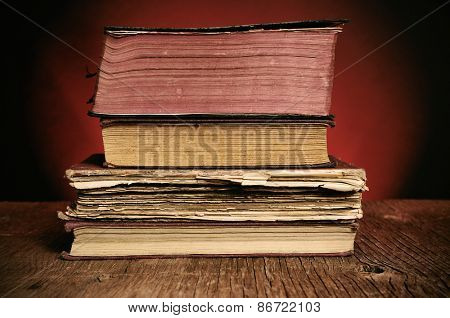 a pile of worn-out old books on a rustic wooden table