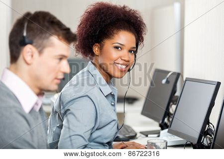 Portrait of confident female employee with male colleague working in call center
