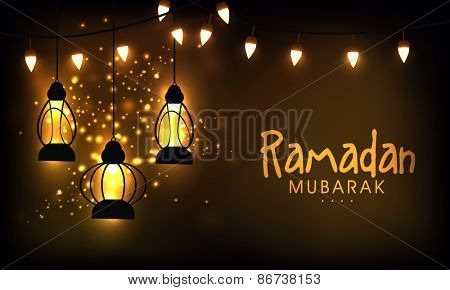 Hanging illuminate lanterns on shiny golden background for the celebration of Islamic holy month of prayers, Ramadan Mubarak.