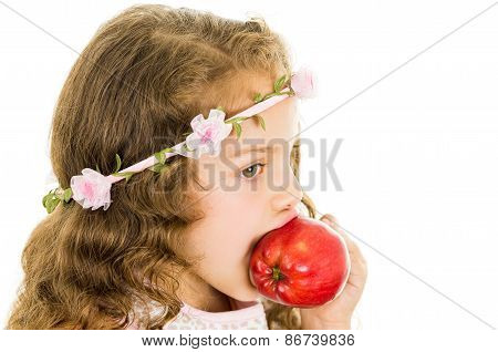 Beautiful healthy little curly girl enjoying eating a red pepper capsicum