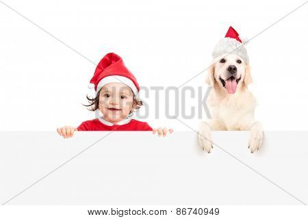 Baby girl in Santa Claus costume and a dog with Santa Claus hat posing behind a blank white billboard isolated on white background