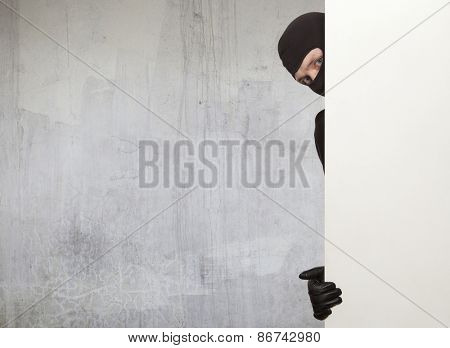 Ninja. Robber hiding behind a empty white sign with space for text