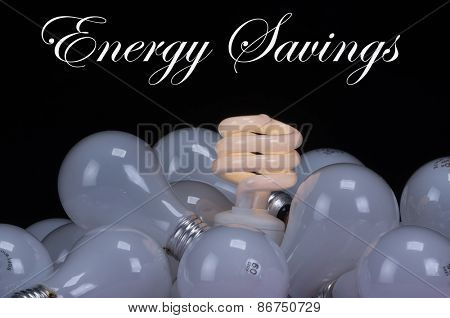 A pig-tailed fluorescent energy saving, green energy, low carbon footprint light bulb nestled in a group of old incandescent bulbs over a black background with room for your text
