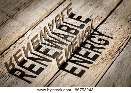 wooden letters on old aged wooden table build the shadow word renewable energy vintage style poster
