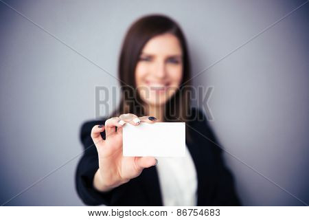Woman holding blank card over gray background. Focus on card