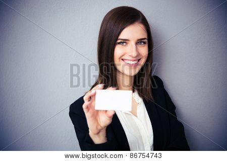 Woman holding blank card over gray background. Focus on woman. Looking at camera