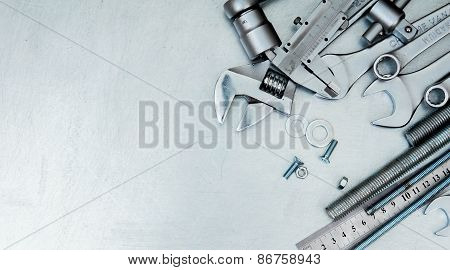 Metal tools and fixing elements on the scratched metal background.