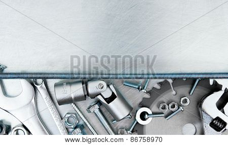 Metal frame and many working tools on the scratched metal background.