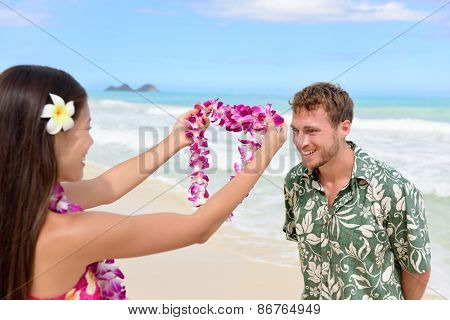 Hawaii woman giving lei garland of pink orchids welcoming tourist on Hawaiian beach. Portrait of a Polynesian culture tradition of giving a flower necklace to a guest as a welcome gesture. poster