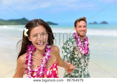 Happy Hawaii beach holiday couple in Aloha shirt and dress and wearing Hawaiian flower leis as a Polynesian culture tradition for welcoming tourists or for a wedding or honeymoon vacation.