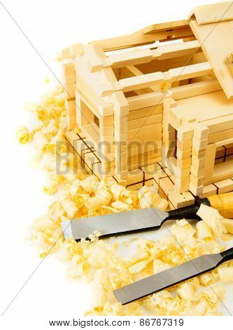 House construction. Joiner's works. The wooden house, chisel and shaving on white background.