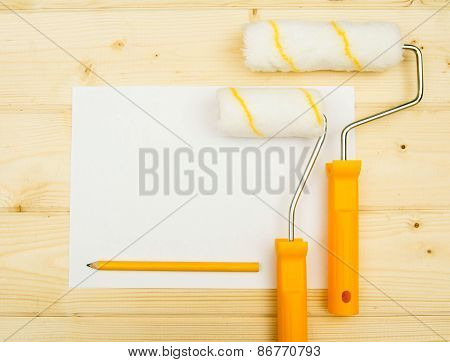 Paper with pencil and platen for paint on wooden background.