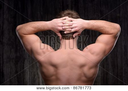 Close up of sporty man demonstrating back muscles