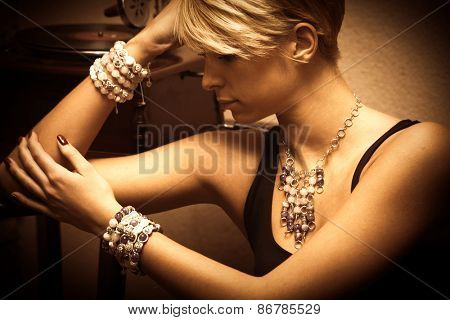 short hair blond elegant young woman portrait wearing jewelry, necklace and lot of bracelets, indoor shot, side view