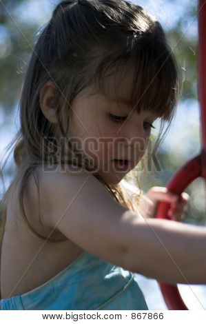 Young Brunette Girl Climbing On Playground Equipment